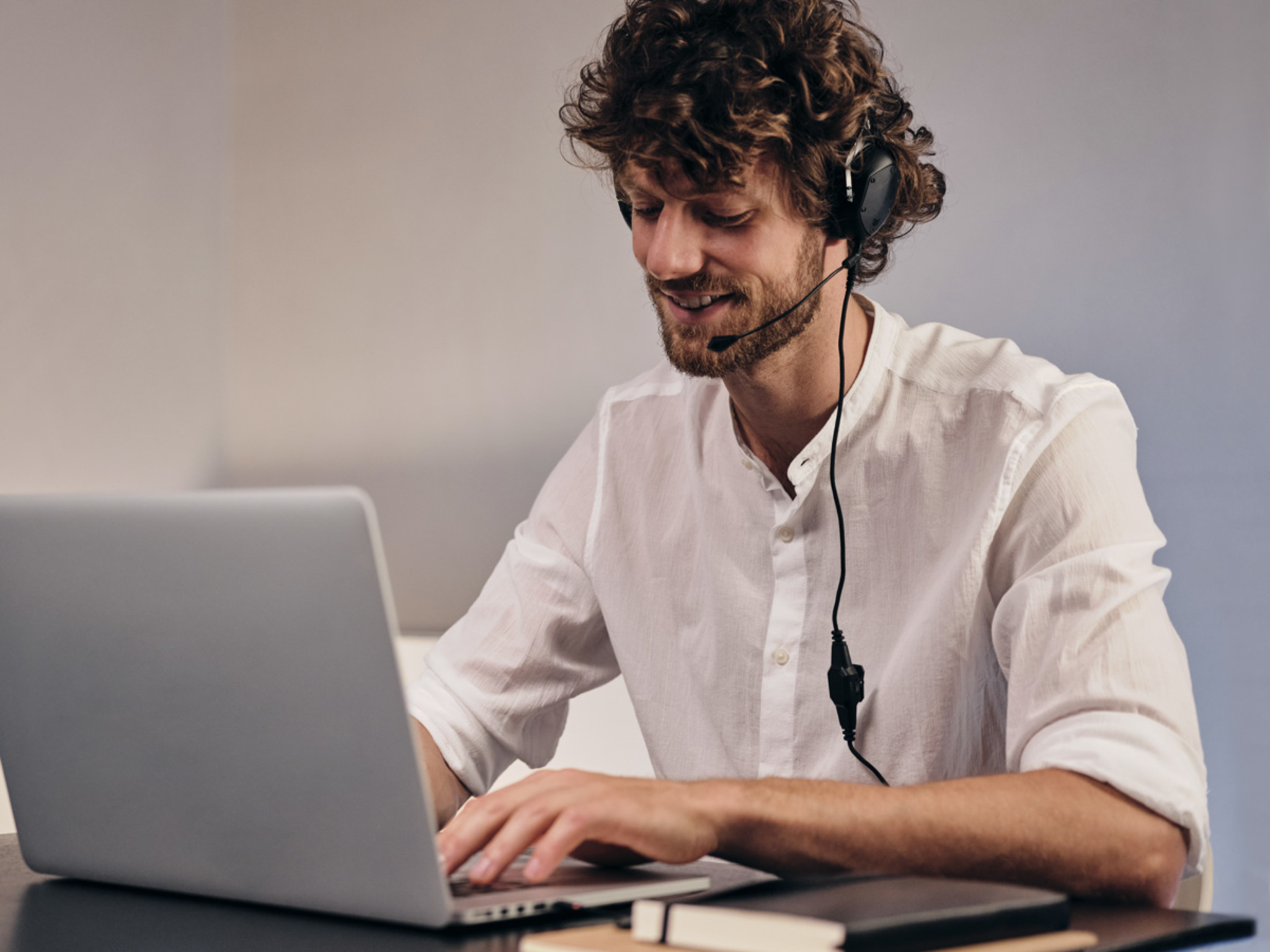 Man using XS and BoomPro Microphone to work from home