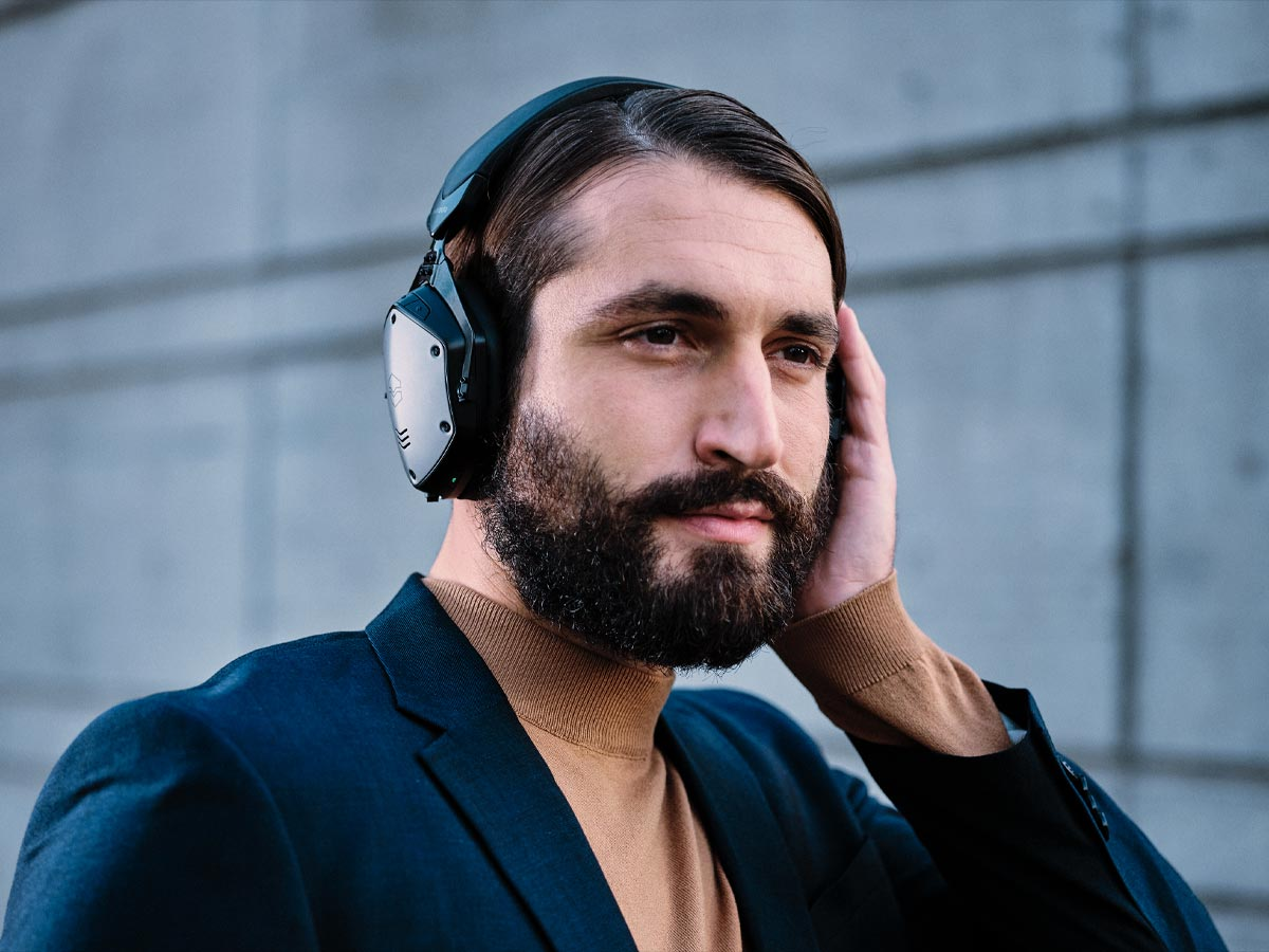 Man wearing M-200 ANC and covering left ear cup to activated Voice In feature