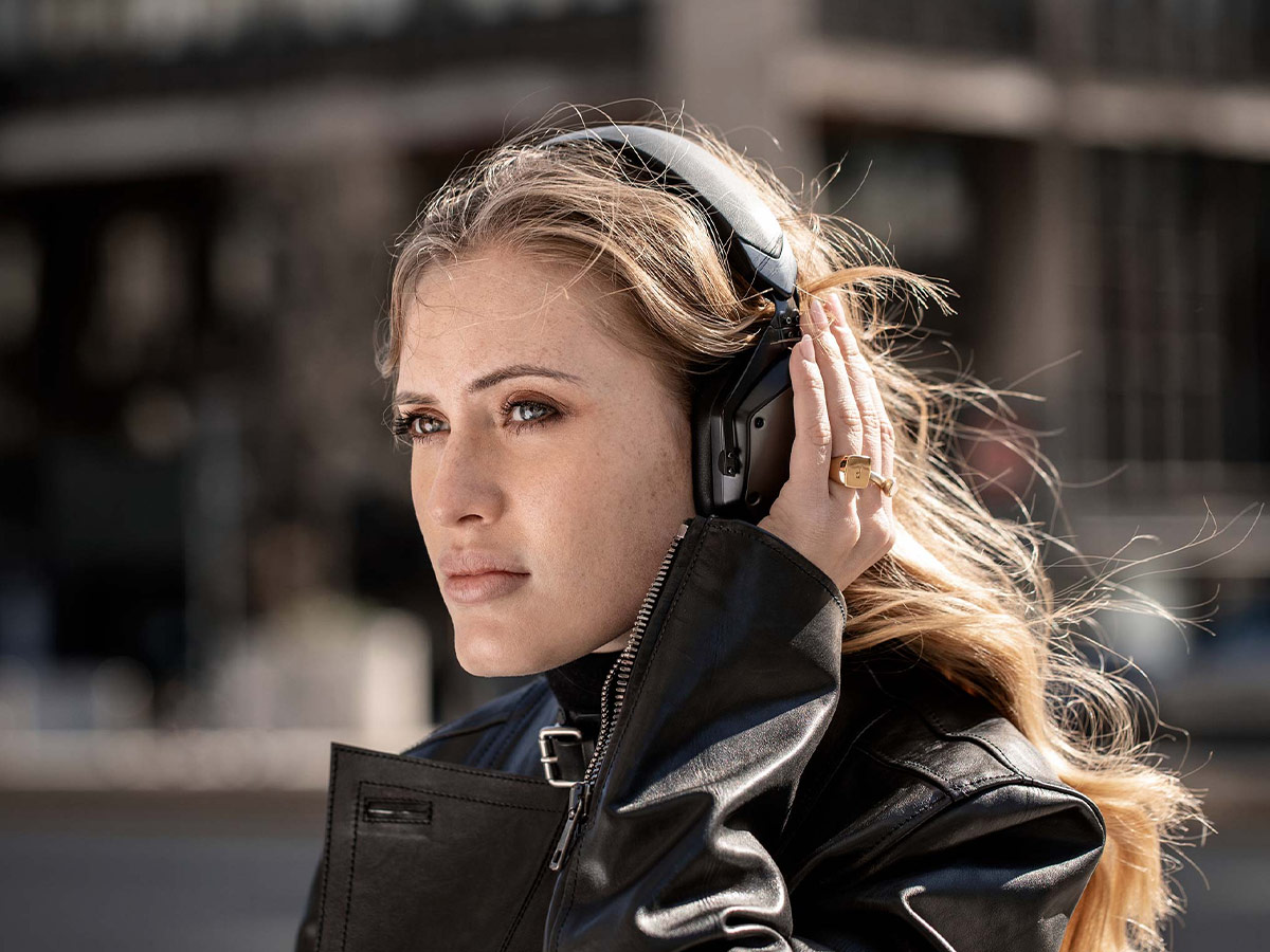 Woman wearing M-200 ANC and covering left ear cup to activated Voice In feature